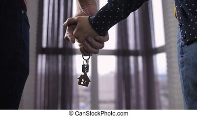 Close-up couple holding hands with new home keys - Close-up...