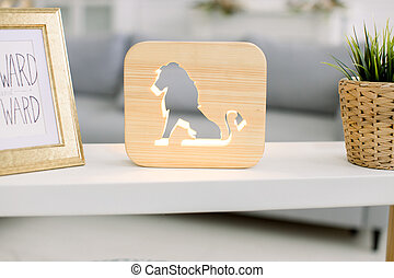Close up cropped image of decorative wooden night lamp with lion picture, on light table with flower pot and photo frame, at cozy living room interior