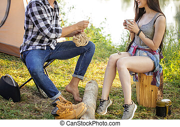 man is uncoiling the rope while a beautiful girl drinking tea