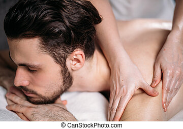 woman's hands doing massage to handsome unshaven man - close...