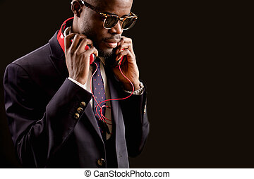 man in formal clothes with red headphones on his neck