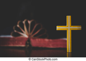 Close up cross with heart shape from holy bible on wooden table. Christian concept