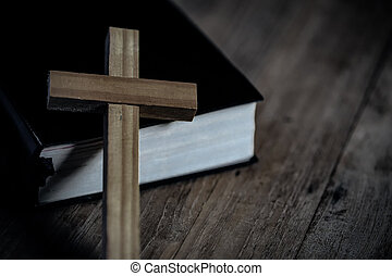 Close up cross with holy bible on wooden table. Christian concept