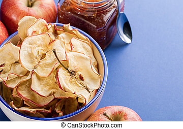 Close-up cup with apple chips, fresh apples and jar of apple jam and metallic spoon on blue background.