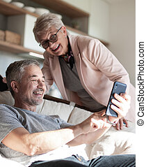 cute elderly couple looking at photos on their smartphone .
