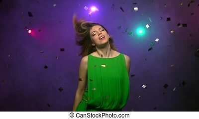 Close-up dancing of young woman in green dress. Slow motion