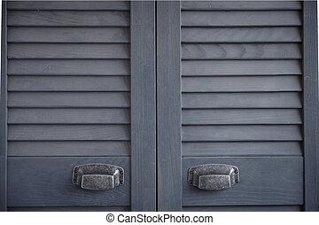 Close up dark gray shutter doors with frayed metal handles, Scandinavian minimalist cabinet interior, selective focus