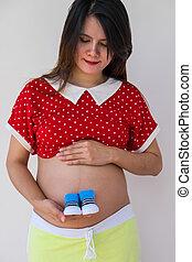 close-up, de, um, mulher grávida, prendendo bebê, sapatos, em, hands., preg