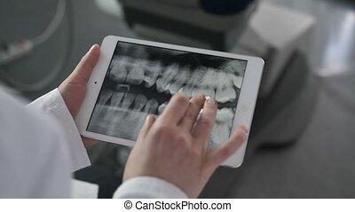 Close-up dentists looking at x-ray on tablet - Close-up of...