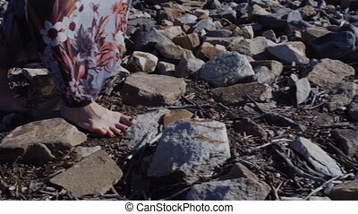 Close up detail of a woman's feet in a long dress standing on big stones with ground