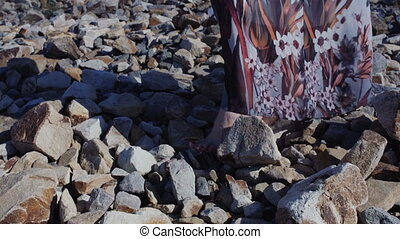 Close up detail of a woman's feet in a long dress standing on big stones