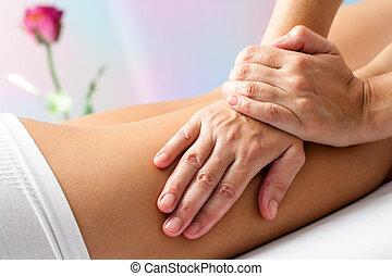 Detail of Hands massaging female hamstrings.