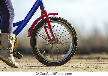 Close-up detail of little girl child feet on a child bicycle