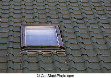 Close-up detail of new small attic plastic window installed in dark green shingled house roof background. Professionally done building and construction work, roofing and installation concept.