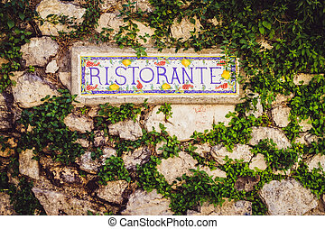 Close up detail of the sign Ristorante on the stone wall in vintage style