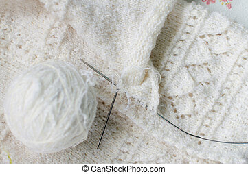 close up detail of white wool woven handicraft knit baby sweater design texture and clew. Fabric white copy space background
