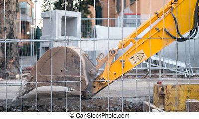 Close up detail view of the shovel bucket attachment of a yellow digging excavator tractor vehicle in motion destroying