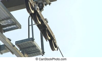 Close up details of metal pulley mechanism on ski lift wire system for transportation skiers and snowboarders on snow mountain in ski winter resort. Rollers and pulleys ski elevator.