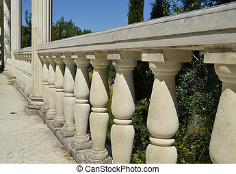 Close-up details of the balustrade, white marble columns, illuminated by the sun