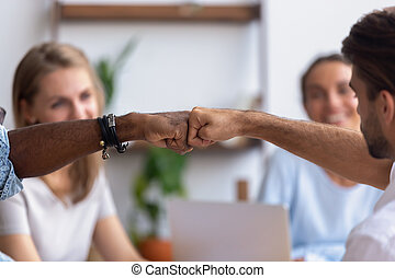 Close up diverse male hands, colleagues giving fist bump