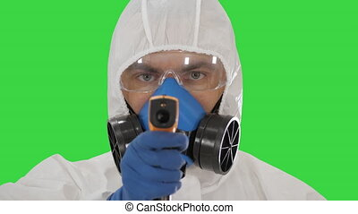 Doctor in protective biohazard suit points laser thermometer to check your temperature at a covid19 checkpoint on a Green Screen, Chroma Key.