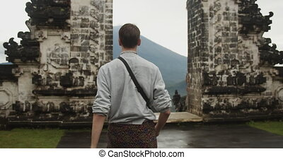 Close up dolly medium view of a white male tourist walking towards the Gates of Heaven tourist attraction in Pura Penataran Agung Lempuyang temple and Mount Agung volcano in Bali 4K
