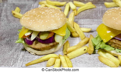 Close up dolly shot on fresh home made burgers on wooden background with golden french fries