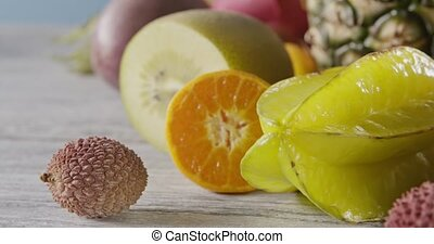Close-up dolly slow motion of passion fruit, carambola,...