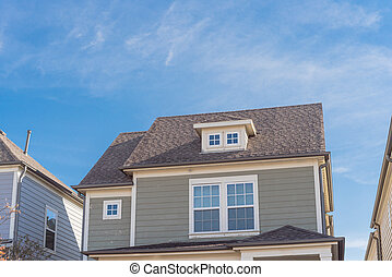 Close-up dormer roof windows on second story of typical houses near Dallas