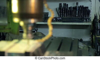 Close up drilling machine drill with holes in metal plate at factory