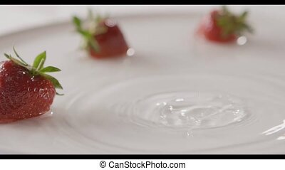 Close-up drops of water and ripe red strawberry fruit falls into a plate with splashes. A few berries lie on the white plate. Slow motion. Soft focus. Full HD video, 240fps,1080p.