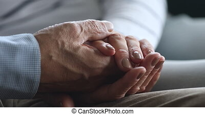 Close up elderly woman holding wrinkled hand of retired husband.