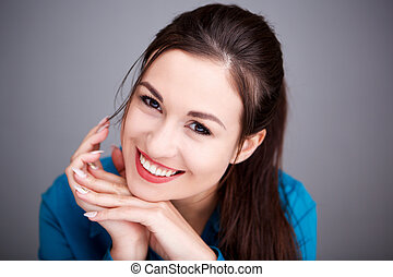 Close up elegant young woman smiling against gray wall