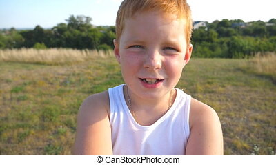 Close up emotions of male child with glad expression on face. Portrait of happy red hair boy with freckles outdoor. Adorable handsome baby looking into camera with joyful smile. Slow motion