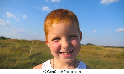 Close up emotions of male child with glad expression on face. Portrait of happy red hair boy with freckles laughs outdoor. Adorable handsome baby looking into camera with joyful smile. Slow motion