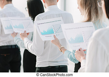 close up. employees with financial data standing in a row