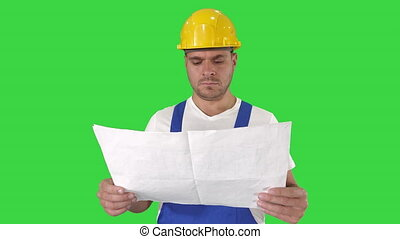 Engineer or Architect or Construction Worker holding blueprint and looking in the result of the work on a Green Screen, Chroma Key.