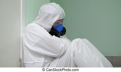 Close up. Exhausted Male Doctor Wearing Hazard Suit Sitting Against Wall. Professional shot in 4K resolution. 054. You can use it e.g. in your commercial video, medical, business, presentation, broadcast