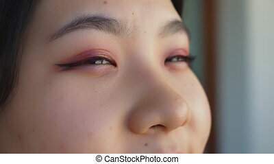 Close up, Eyes of happy young asian woman with pink eyeshadow looking through the window. High quality 4k footage