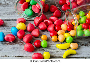 Close-up f red and yellow candies scattered from jars