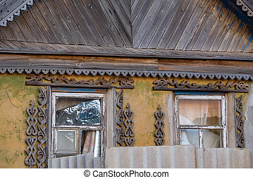 Close up facade of old rural house. View of broken windows with wooden decoration