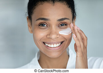 Close up face 35s young adult African ethnicity beautiful woman apply facial day or night cream smile looking at camera. Professional cosmetics skin care remedy, beauty treatment advertisement concept