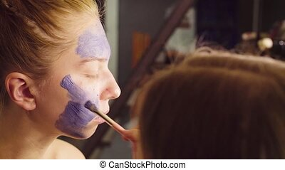 Face art. The make-up artist begining to paint