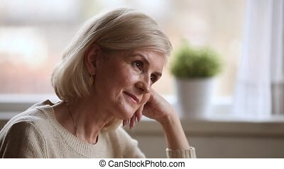 Close up face elderly woman smiling thinking lost in...