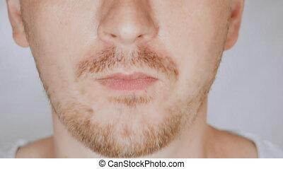 close up face fair man eats bell pepper - details lower face...