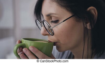Close-up face of a young girl in glasses for the image, she drinking hot tea with lemon