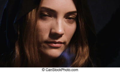 Close-up face of a young woman in a halloween hood extinguishes a candle blowing out and looking at the camera while flirting