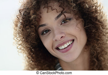 Close-up face of beautiful young woman with curly hair