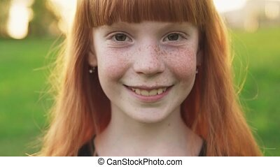 Close-up face of happy ginger girl with freckles on blurred background