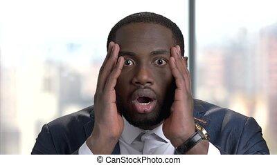 Close up face of shocked dark-skinned businessman....